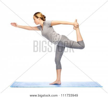 fitness, sport, people and healthy lifestyle concept - woman making yoga in lord of the dance pose on mat