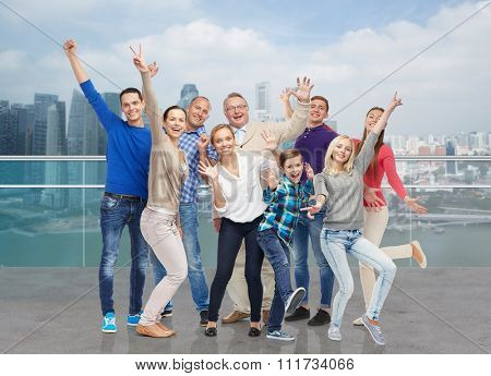 family, gender, generation and people concept - group of happy men, women and boy having fun and waving hands over singapore city waterside background