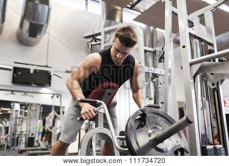 sport, bodybuilding, equipment and people concept - young man with barbell flexing muscles on t-bar row machine in gym