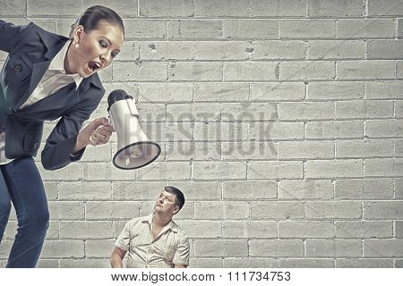 Aggressive businesswoman screaming in megaphone on her colleague
