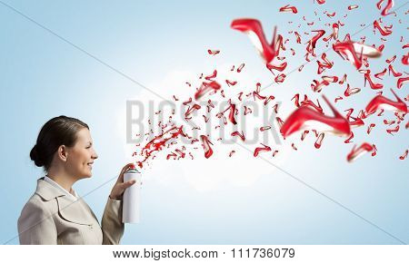 Young businesswoman spraying red shoes from aerosol balloon