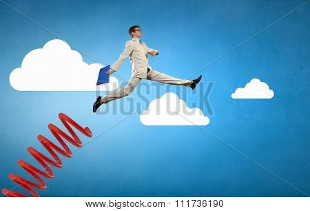 Businessman jumping on springboard as progress concept