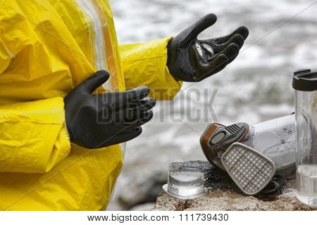 scientist in mask and protective uniform examining  little fishes on hand in glove