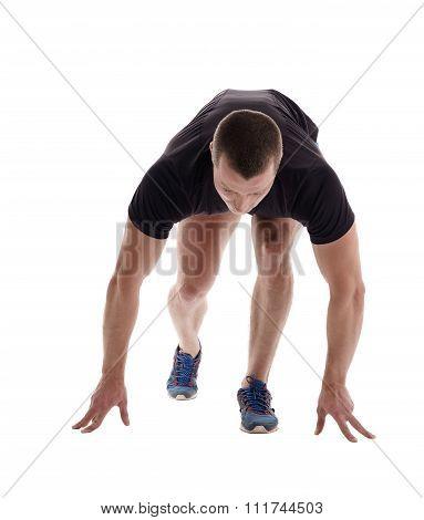 Male sprinter posing on starting block