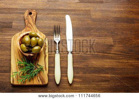 Fresh olives on rustic wooden background.  Olives in olive wood.