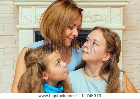 Mother And Her Two Daughters Sitting Near The Fireplace.