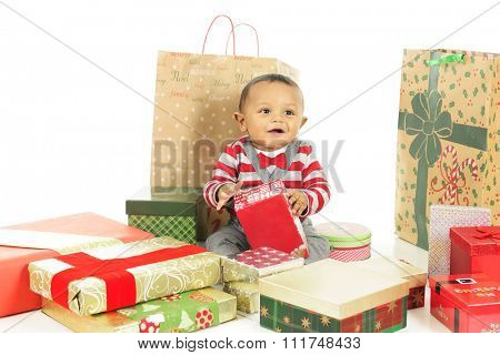 An adorable, dressed up baby boy enjoying the wrapped gifts that surround him.  On a white background.