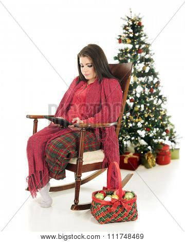 A beautiful teen girl snuggled up in her pajamas, using her ipad in a vintage rocking chair.  A basket of ornaments are by her side and a lighted Christmas tree is behind her.  On a white background.