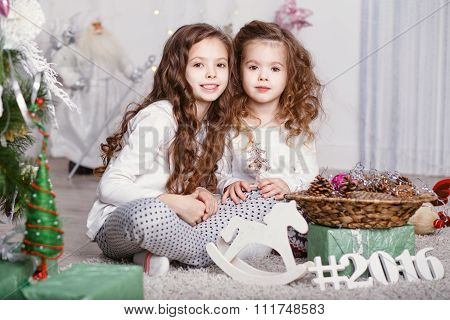 Two Little Girls In A Comfortable Home Clothes Sitting On The Floor In The Beautiful Christmas Decor