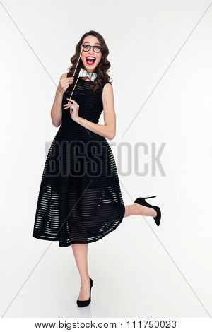 Full length of charming elated curly young retro styled girl in black dress and shoes posing with fake paper glasses and bow tie props over white background