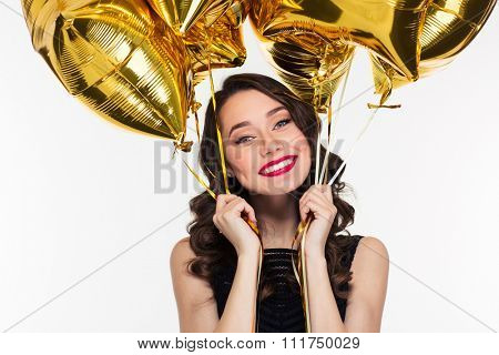 Cheerful happy beautiful young woman in retro style holding golden balloons over white background