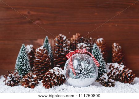 Christmas And New Year Background With Snow, Pinecones, Christmas Ball With Snowflake.