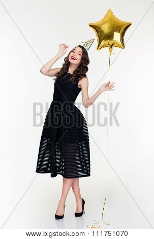 Attractive happy young woman in retro style posing with birthday hat prop on stick and star shaped balloon over white background