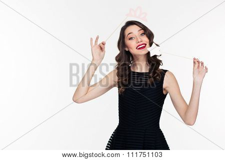 Attractive happy smiling young woman with bright makeup in retro style using fake crown props and magic stick over white background