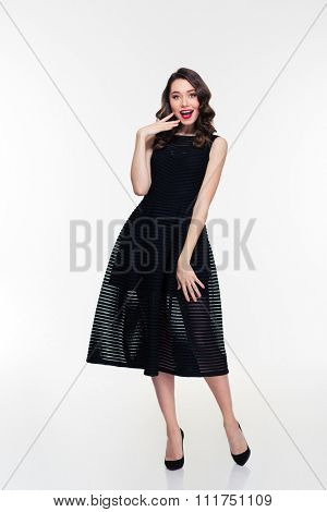 Full length portrait of smiling lovely surprised girl with retro hairstyle in black dress and shoes isolated over white background