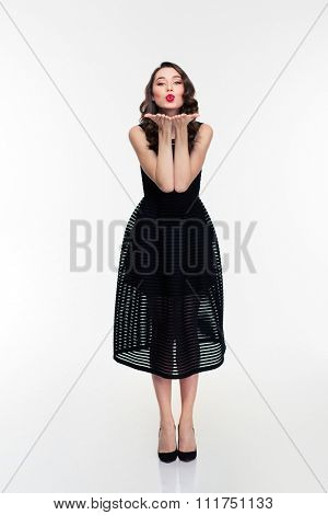 Full length of beautiful positive young woman in retro style sending a kiss isolated over white background