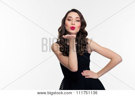 Portrait of attractive cute girl with bright makeup in retro style sending a kiss isolated over white background