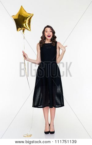 Surprised elated curly retro styled young woman in black dress and shoes with golden star shaped balloon isolated over white background