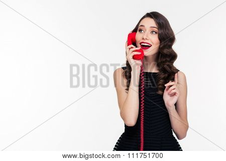 Happy attractive young curly woman with retro hairstyle in black dress talking on telephone over white background