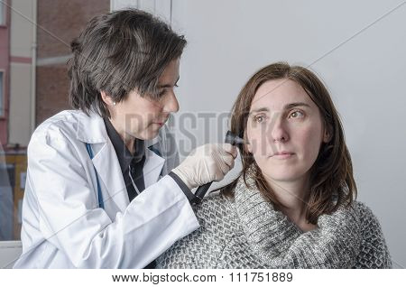 Female Doctor Using Otoscope With A Girl Patient.