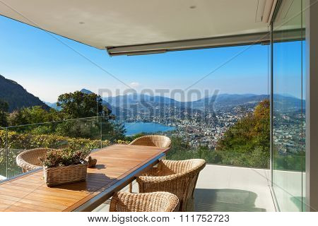 beautiful veranda with wooden table and wicker chairs, panoramic view