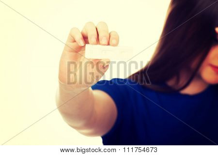 Unhappy teenage woman holding pregnancy test.