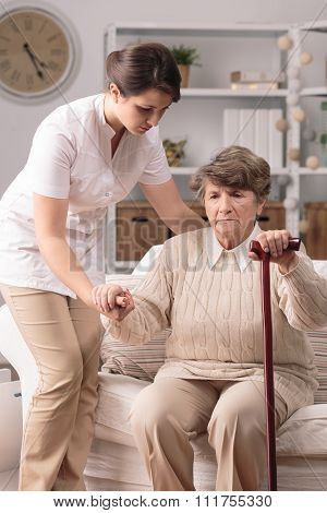 Carer Helping Senior With Stick