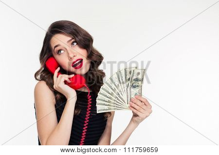 Attractive joyful curly young female with bright makeup in retro style holding money and talking on telephone