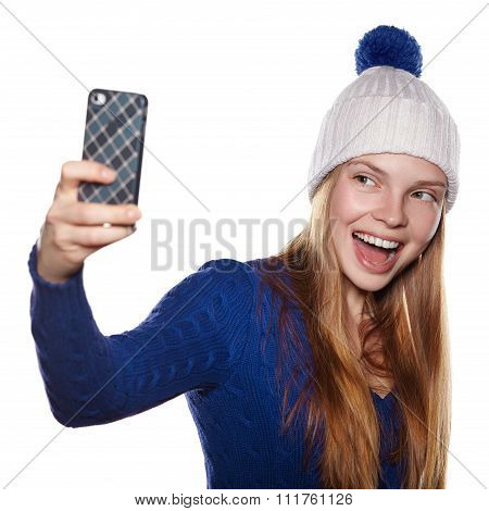 Young girl in winter hat laughing and making selfie.