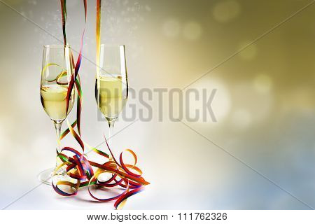 Flutes Champagne Glasses And Colorful Streamers Against A Bokeh Background For New Years Eve