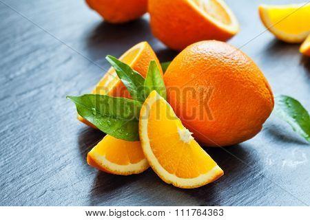 Fresh orange fruit placed on black stone.