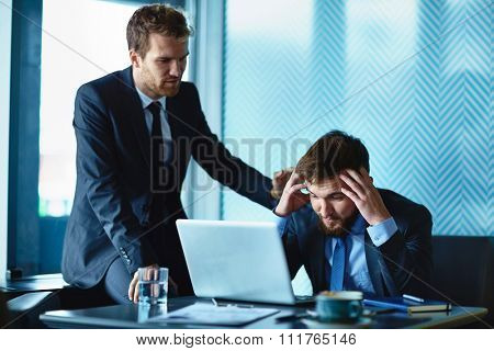 Young businessman reassuring his frustrated colleague