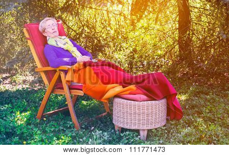 Older Woman Sleeping In Chair In The Garden