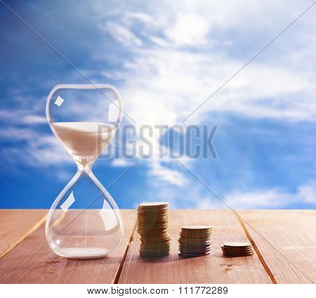 Hourglass with coins on wooden table on bright background