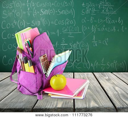 Backpack with school supplies on wooden table on green desk background