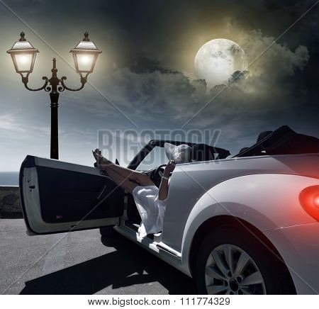 Woman resting at night on the waterfront in the car.
