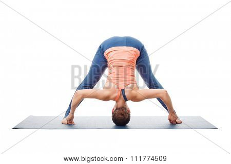 Beautiful sporty fit woman practices Ashtanga Vinyasa yoga asana Prasarita padottanasana D - wide legged forward bend D isolated on white background