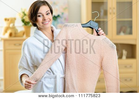 Teenage girl holding a woolen sweater.