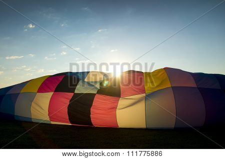 Sun Peaking Over The Inflating Envelope Of A Hot Air Balloon