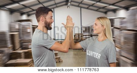 Smiling volunteer doing high five in office against many stack of cardboard boxes