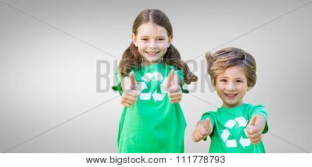 Happy siblings in green with thumbs up against grey vignette