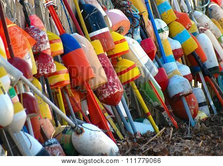 A collection of buoys leaning against a fence