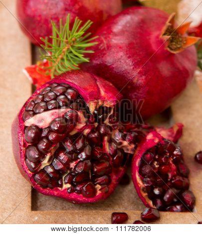 Fresh ripe pomegranates on wooden background and Christmas decoration.