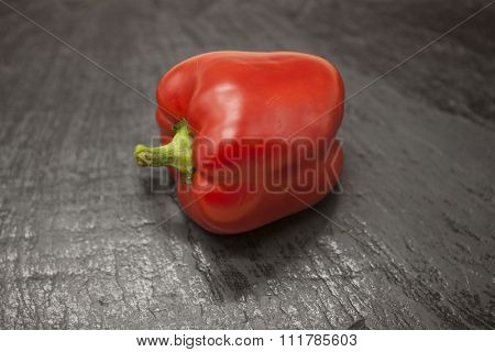 Fresh juicy red sweet pepper close up on a stone background.