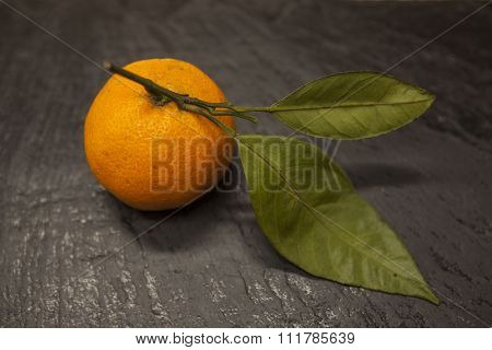 Fresh juicy tasty Sicilian tangerine with a foliage branch on a stone background