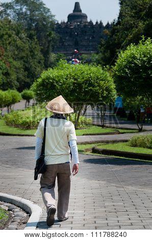 Man with straw hat walking towards Borobudur temple