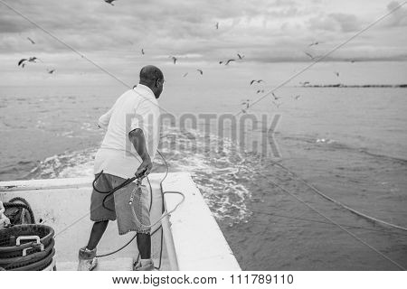 BEAUFORT, SOUTH CAROLINA-OCTOBER 16, 2015: Unidentified worker throws a hook to catch a net on a fishing vessel in South Carolina.