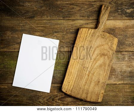 chopping board and empty page on rustic background