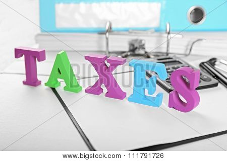 Alphabet TAXES with calculator and papers on table