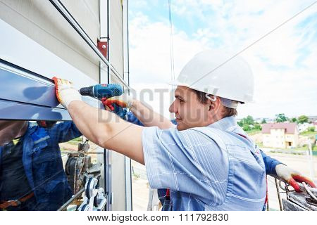 worker builder with hand drill installing glass windows on facade of business building
